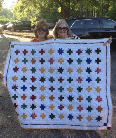 Two women smile, holding a quilt with 80 stars.