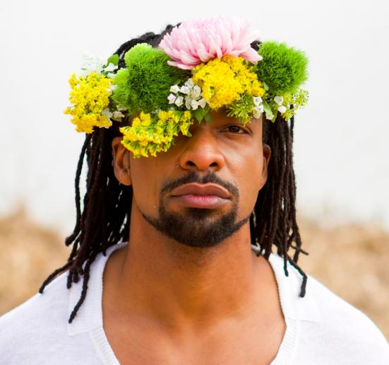 A man with dark braids and medium skin wears a flower crown.
